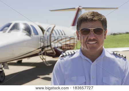Hispanic pilot standing outside private jet