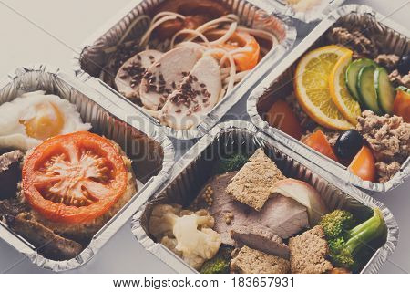 Healthy food delivery. Take away of natural fitness dishes for diet. Daily meals in foil boxes on white, vintage filter