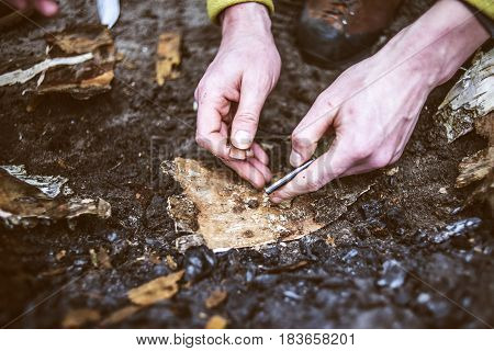 Man hands trying to make fire by flint in a forest.