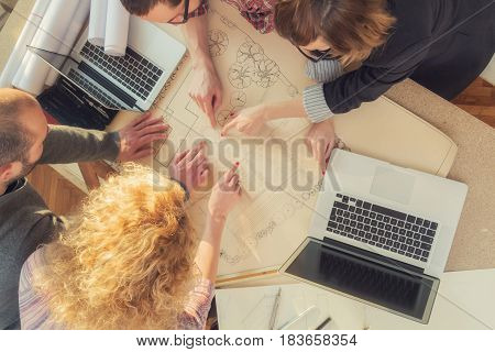 Group of ordinary young people discussing business plans with lap-tops plans in a room lit by natural sunlight.