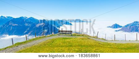Bench on top of the mountain. Grandiose panorama of mountains and clouds from the top.