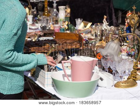 LINZ, AUSTRIA - MARCH 25, 2017: Young girl looking for old vintage furniture and photos at the flea market in Hauptplatz in Linz, Austria