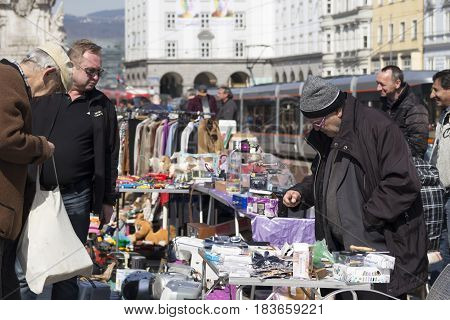 LINZ, AUSTRIA - MARCH 25, 2017:  Old Austrian man selling electronic accesories in the Hauptplatz Fleamarket in Linz, Austria
