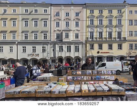 LINZ, AUSTRIA - MARCH 25, 2017:  Austrian man selling second hand music cds in the Hauptplat Fleamarket in Linz, Austria