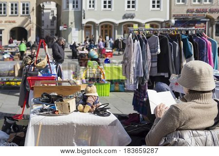 LINZ, AUSTRIA - MARCH 25, 2017:  Austrian woman reads a book while selling old vintage objects in the Hauptplatz Fleamarket in Linz, Austria