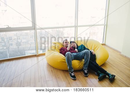 Young beautiful man and girl resting in a room with a modern interior. They use a mobile phone. Bag chair in a modern beautiful office