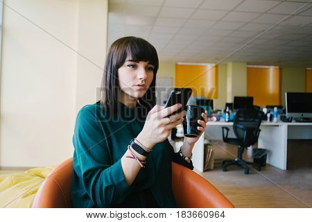 Young and very beautiful business woman uses phone and holding a cup of coffee. Against the background of office jobs. Break in the modern office.