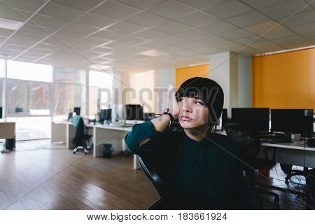 Young beautiful woman office worker with a sad face. She is very tired and waiting for the end of the day. Office life difficult