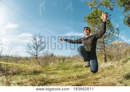 A man at the age of sitting on slackline, catching balance and enjoying life