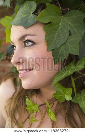Hispanic woman standing near ivy