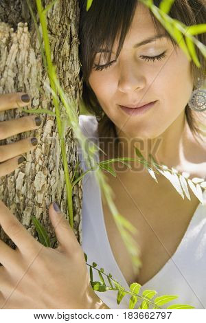Hispanic woman hugging tree