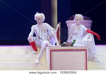 Blond with a blonde with white faces, in a white dress, depict a statue