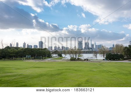 green meadow in central park with Shanghai cityscape in background.