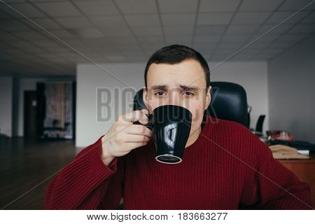 Portrait of a young man sitting on workplace with cup of coffee in hand. Sleepy office worker