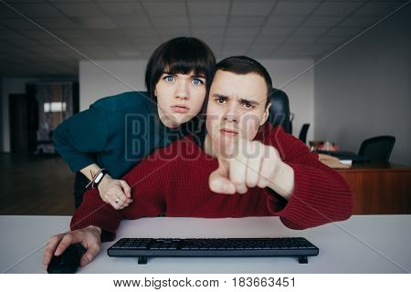 Young man showing something business woman on the computer screen.