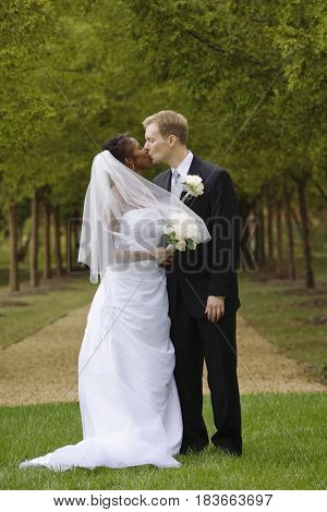 Bride and groom kissing in grass