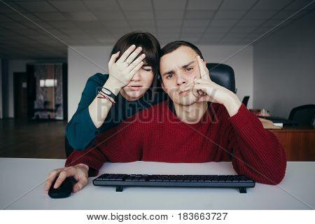 Young office workers made a mistake and therefore very disappointed. Emotional beautiful young people in the workplace. The situation in the modern office