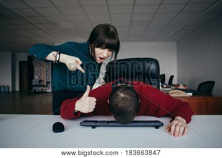 Business woman yells at his subordinate who lowered his head and shows paletst up. The situation in the office. Young office workers quarreling.
