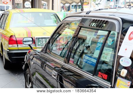 TOKYO, JAPAN - APRIL10, 2017 :Taxi cars on the street near the ueno station in Tokyo on APRIL10, 2017 in Tokyo, Several taxi cabs are waiting in line along the sidewalk.