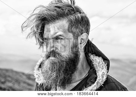 Bearded Man On Windy Mountain Top On Natural Cloudy Sky