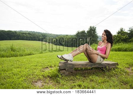 Hispanic woman sitting on rock in field