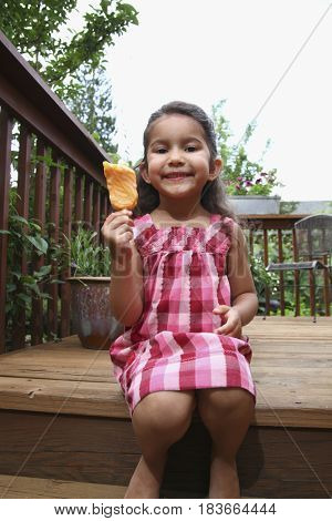 Mixed race girl eating popsicle