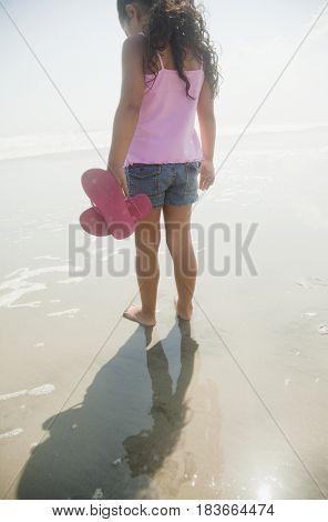 Hispanic girl walking on beach