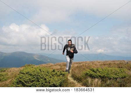 man runs on the green meadow in mountain on cloudy sky background