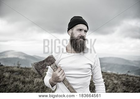 bearded man long beard brutal caucasian hipster with moustache holds axe with serious face on mountain top with cloudy sky unshaven guy with stylish hair getting beards haircut on natural backdrop