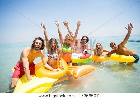 Portrait of cheerful friends enjoying on inflatable rings and pool rafts in sea