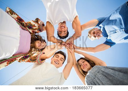 Directly below shot of friends huddling with arms raised against sky on sunny day