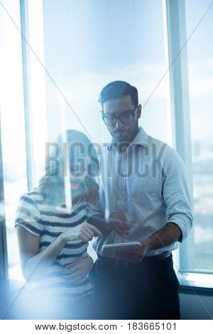 Business couple using digital tablet against glass window in office
