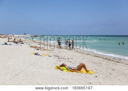 Tourists Sunbath, Swim And Play On South Beach In Miami Beach, Florida