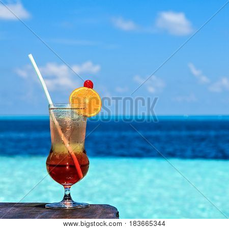 Glass of the soft drink is on a beach table (Maldives The Indian Ocean)