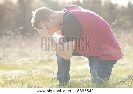 Man on one knee praying in outdoor setting