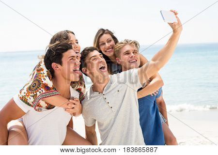 Cheerful friends taking selfie at beach on sunny day