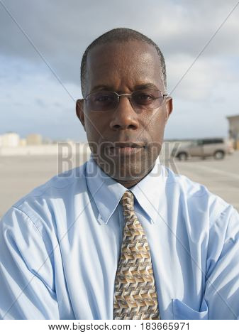 African businessman standing in parking lot
