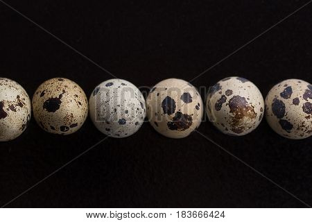 Quail Eggs On A Black Background.