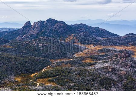 Winding Dirt Road And Rocky Cliffs At Mount Buffalo National Park, Victoria, Australia