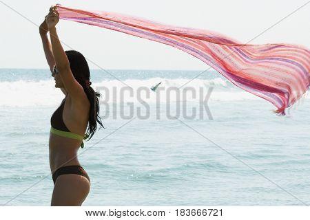 Hispanic woman holding scarf on beach