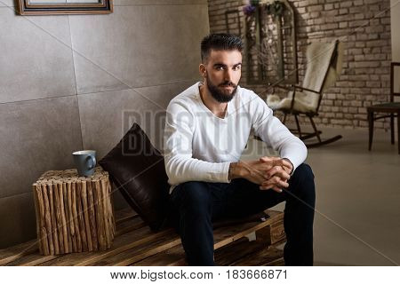 Portrait of bearded man sitting on pallet furniture at home.