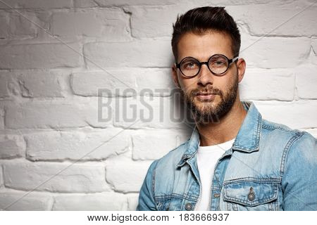 Portrait of smart young goodlooking man wearing glasses leaning against white brickwall. Lots of copyspace.