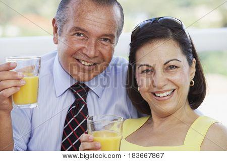 Hispanic couple drinking orange juice