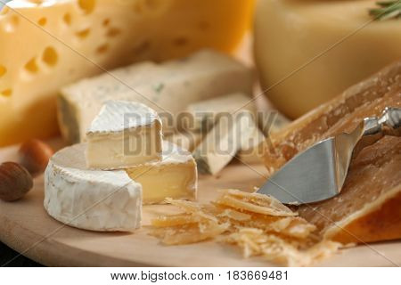 Wooden board with different types of cheese, closeup