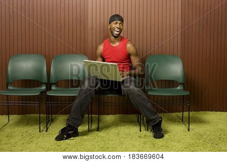 African man using laptop and laughing