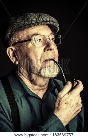 Portrait of a smiling old man smoking a pipe. Black background. Old age concept.