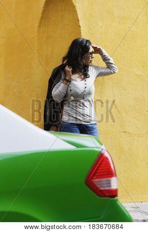 Hispanic woman waiting on sidewalk