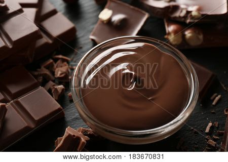 Bowl with melted chocolate and chopped bars, closeup