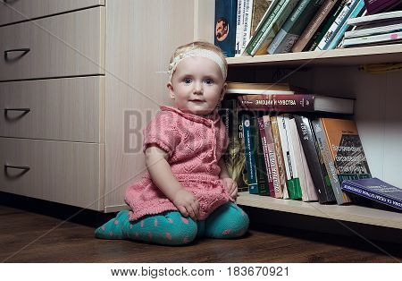 Kiev Ukraine November 17 2016: Child girl sitting near bookshelf in the home library