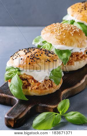 Homemade mini burgers with pulled chicken, basil, mozzarella cheese and yogurt sauce on wooden serving board over gray texture background. Close up. Healthy fast food concept
